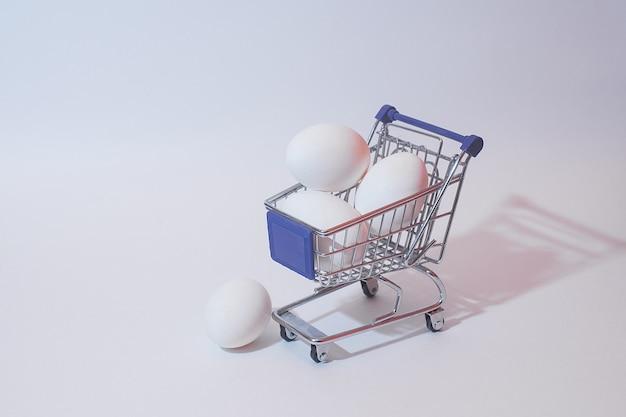 Wit ei in een stuk speelgoed karretje voor producten op een witte achtergrond