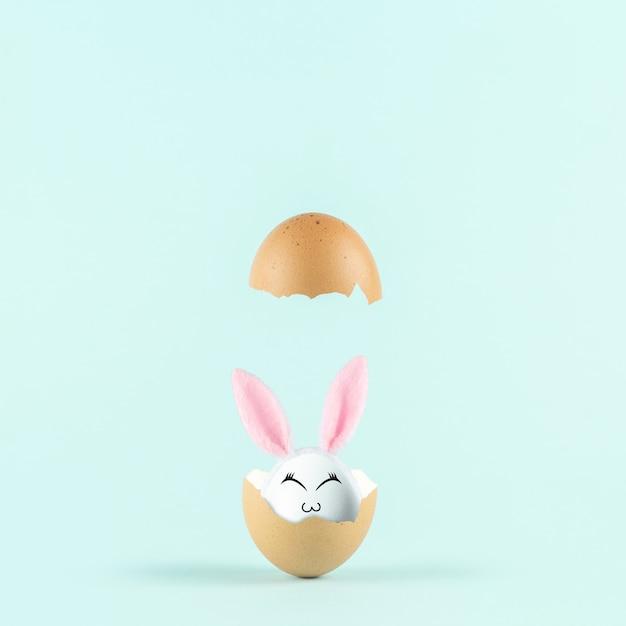Wit ei met konijnenoren in gebarsten eierschaal tegen pastelkleur blauwe achtergrond