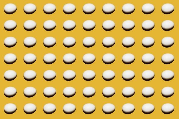 Wit ei op een gele achtergrond. kleurrijk patroon van kippen witte eieren. patroon op een gekleurde achtergrond.