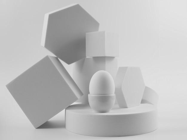 Wit ei op witte platforms, monochroom minimalistisch voedselconcept
