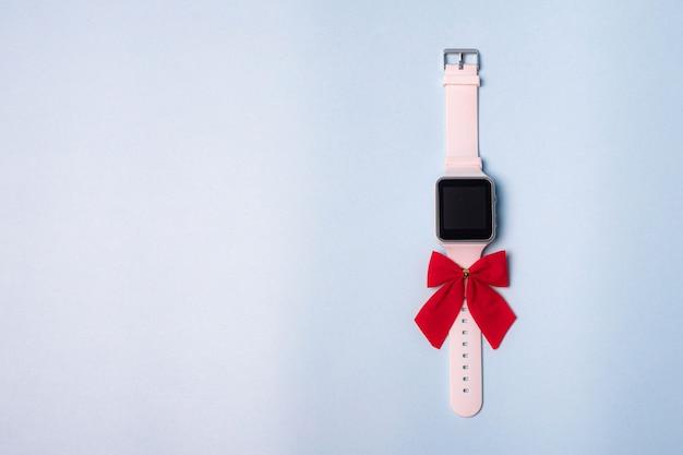 Wit elektronisch horloge met een strik op een effen achtergrond. het horloge is handgemaakt met een strik