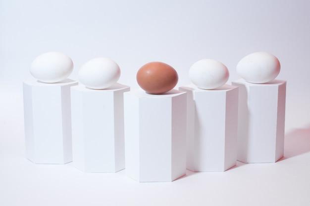 Wit en bruin ei op een witte achtergrond. witte geometrische vormen en eieren. paasvakantie. geïsoleerd