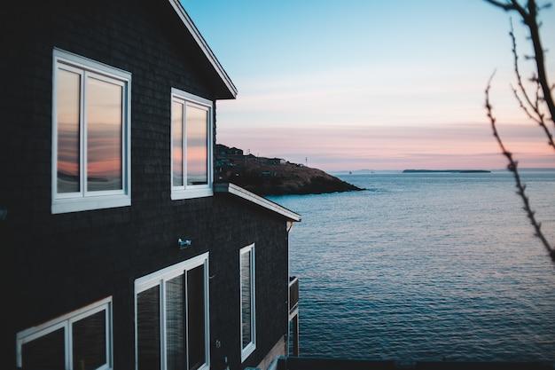 Wit en bruin houten huis dichtbij waterlichaam tijdens zonsondergang