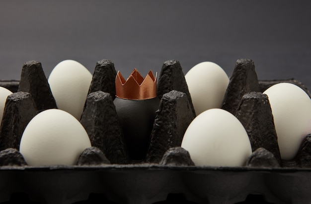Wit en geverfd zwart ei versierd met een papieren gouden kroon in een zwarte kartonnen doos op een zwarte achtergrond met ruimte voor tekst. rijkdom concept