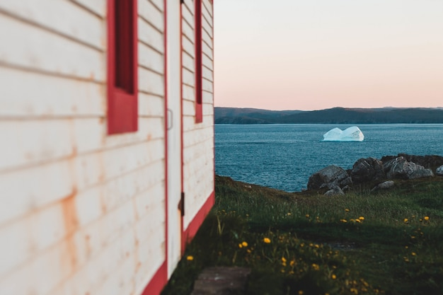 Wit en rood huis op grasberg gedurende dag