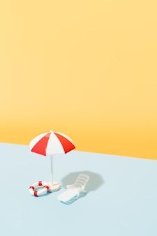 Wit en rood parasol zonnestoel blauw en wit gestreepte handdoek en reddingsboeien