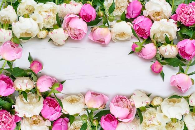 Wit en roze pioenenframe op witte houten achtergrond. copyspace, bovenaanzicht.
