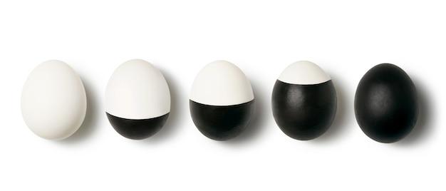 Wit en zwart gekleurde eieren op een witte achtergrond met kopie ruimte. concept van het veranderen van het leven. vlak