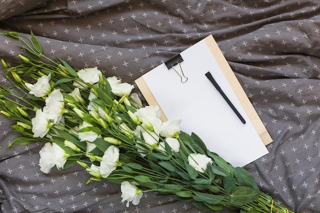 Wit eustoma boeket; klembord en pen op grijze kleding