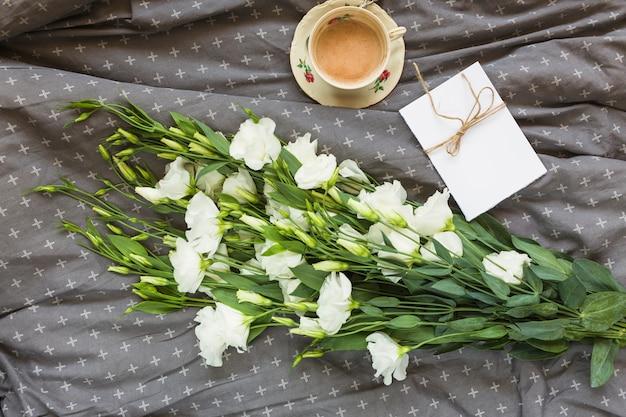 Wit eustoma boeket; koffiekopje en kaart op grijze doek