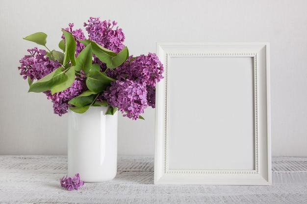 Wit fotolijstje en boeket paarse lila bloemen in vaas. ruimte voor tekst.