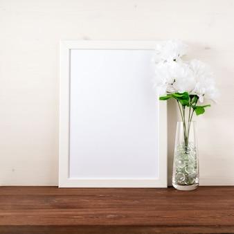 Wit frame, bloem in glazen fles op donkerbruine houten tafel a