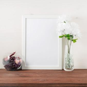 Wit frame, bloem in glazen fles op donkerbruine houten tafel tegen de witte muur