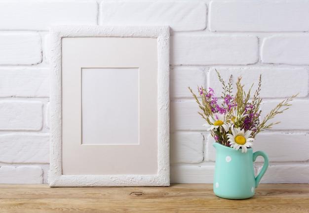 Wit frame met kamille en paarse veldbloemen in muntkan