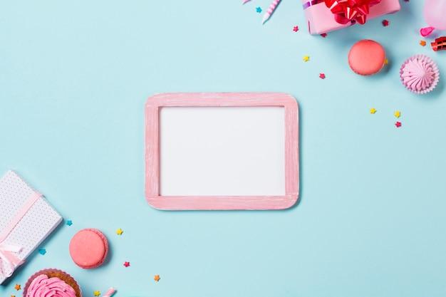 Wit frame met roze houten lijst met feestmuffins; aalaw; bitterkoekjes en geschenkdozen op blauwe achtergrond