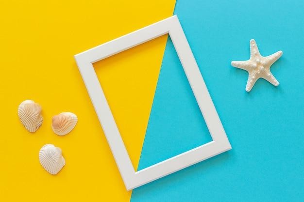 Wit frame met zeester op blauwe, gele achtergrond en zeeschelpen.