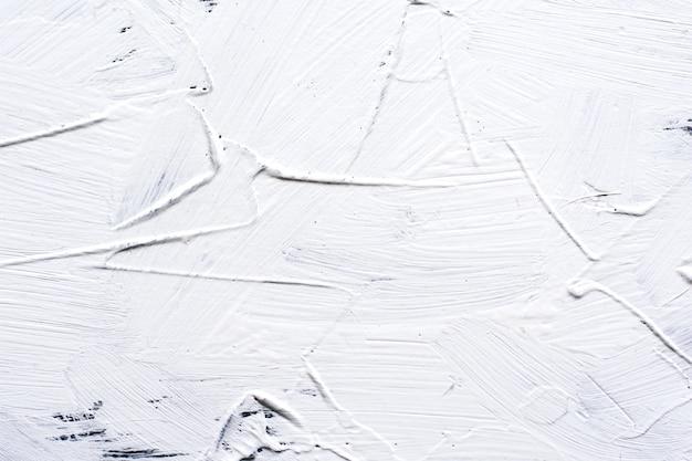 Wit geschilderde cementachtergrond met brede borstelslagen