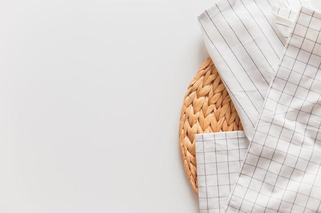 Wit gestreept en geruit tafelkleed en rieten placemat close-up, geïsoleerd op wit met kopie ruimte.