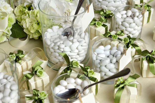 Wit gesuikerde amandelen op glazen en geschenkdozen