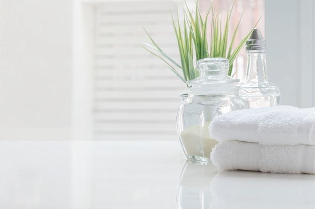Wit gevouwen handdoeken en glazen fles op witte tafel met kopie ruimte op onscherpe badkamer achtergrond.