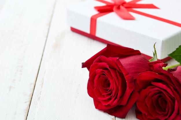 Wit giftvakje en rode rozen op de witte houten ruimte van het lijstexemplaar
