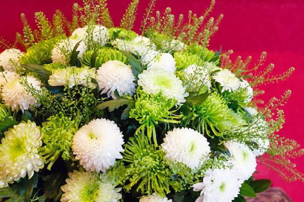Wit - groen chrysant zomerbloemen boeket op rood