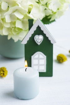 Wit groen houten huis, hortensiabloemen in pot en aangestoken kaarsen