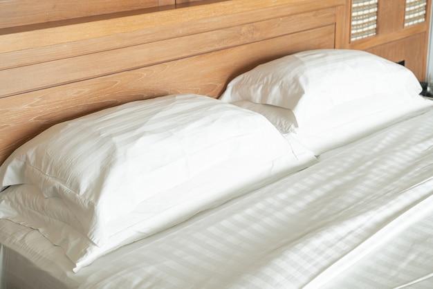 Wit hoofdkussen op het binnenland van de beddecoratie van hotelslaapkamer