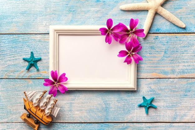 Wit houten fotokader met purpere bloemen op blauwe oude sjofele achtergrond met exemplaarruimte.