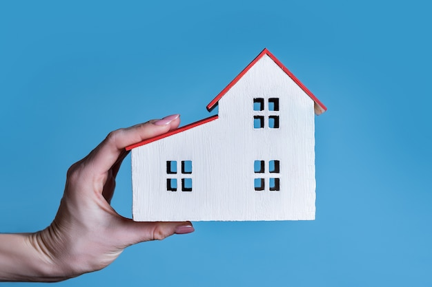 Wit houten huis in een vrouwelijke hand. blauw. huisvestingsconcept