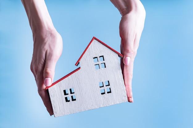 Wit houten huis in vrouwelijke handen. blauwe achtergrond. woonconcept