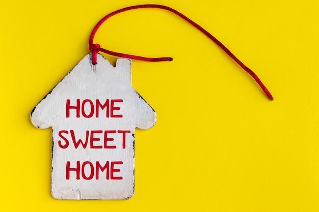 Wit houten huis met inscriptie home sweet home