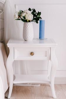 Wit houten nachtkastje, dressoir in slaapkamer. boeket op het nachtkastje vaas met bloemen, kaars. interieur. serie meubels. moderne ontwerper. vintage stijl korte kast met lade in de kamer.
