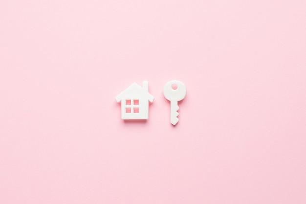 Wit huis en sleutel in een minimale stijl op roze, bovenaanzicht