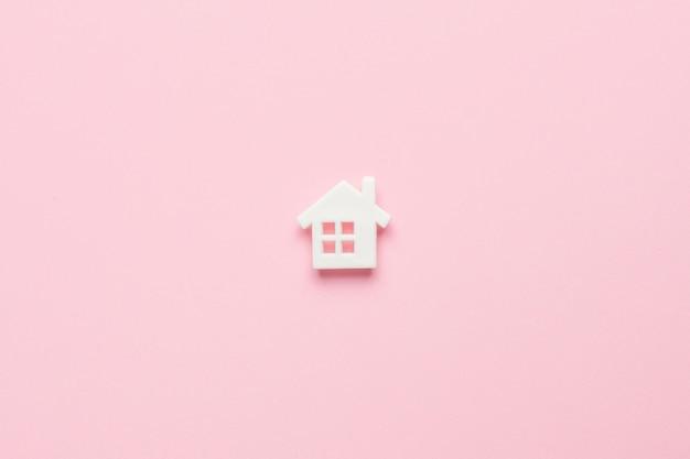 Wit huis in een minimale stijl op roze, bovenaanzicht