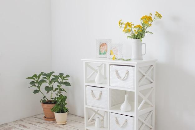 Wit interieur met boeket bloemen met foto's van kinderen op plank