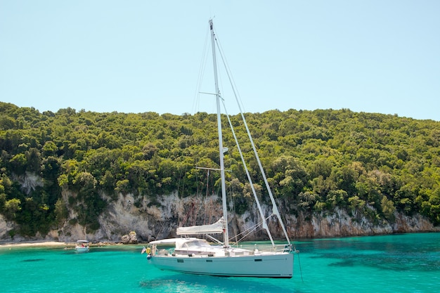 Wit jacht zeilen in de turquoise lagune op een zonnige dag