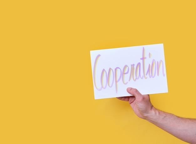 Wit karton met de handgeschreven tekst samenwerking op gele geïsoleerde achtergrond