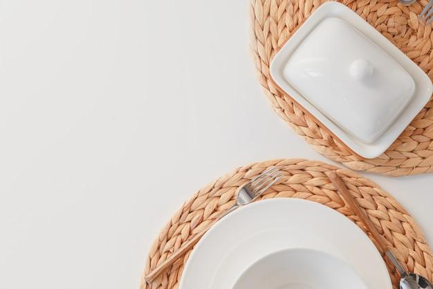 Wit keramisch serviesgoed, gevlochten ronde placemat, bestek en op boterachtige witte achtergrond. scandinavische stijl.