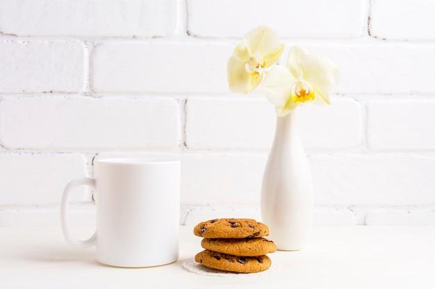 Wit koffiemokmodel met zachte gele orchidee in vaas en koekjes