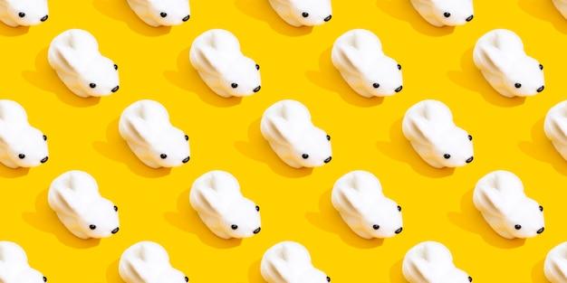 Wit konijn op een geel patroon als achtergrond.