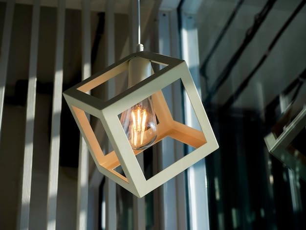 Wit kubiek frame hangend met een gloeilamp. moderne plafondlamp met doosvormig frame, eigentijdse designverlichting in de woonkamer.