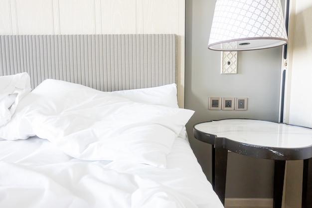 Wit kussen met deken op onopgemaakt bed
