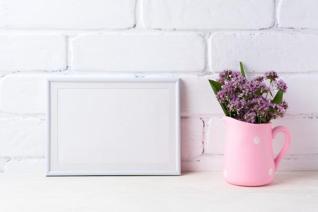 Wit landschapskader met paarse bloemen in stip roze waterkruik
