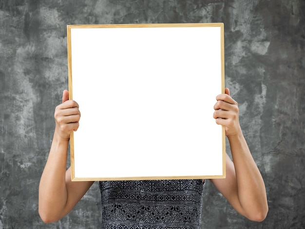 Wit leeg framemodel in vierkant houten frame. vrouw handen met lege vierkante ruimte in houten frame op grunge grijze betonnen muur achtergrond.