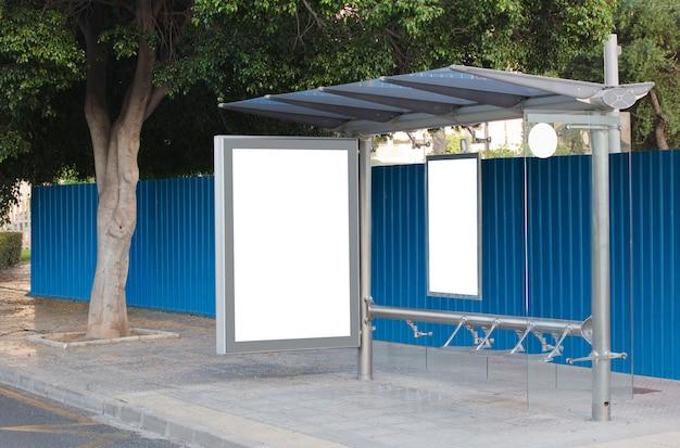 Wit leeg verticaal reclamebord bij bushalte op stadsstraat met blauw reclamebord teken op straat ne