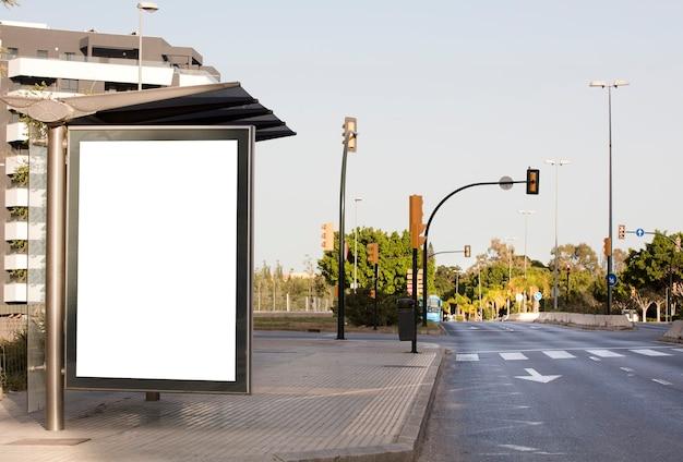 Wit leeg verticaal reclamebord bij de bushalte op de stadsstraat op de achtergrond van bussen en ro