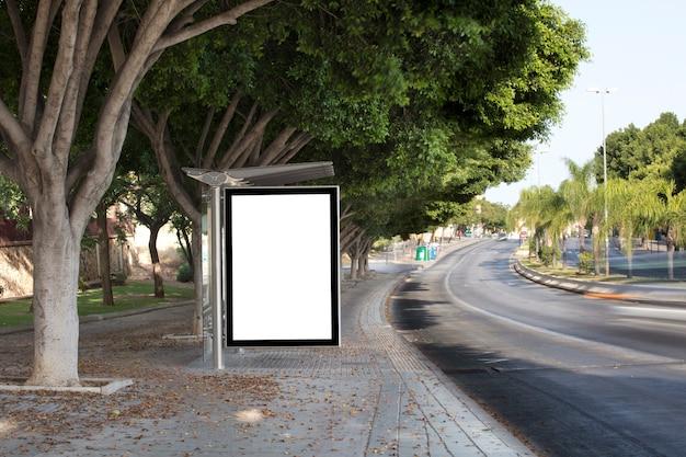 Wit leeg verticaal reclamebord bij de bushalte op de stadsstraat teken op de straat naast
