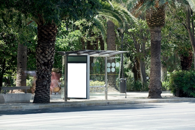 Wit leeg verticaal reclamebord bij de bushalte op de stadsstraat