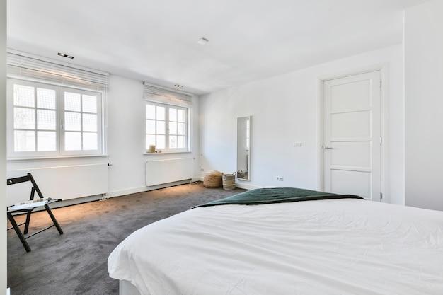 Wit linnen van bed in ruime witte kamer met ramen en spiegel in de hoek